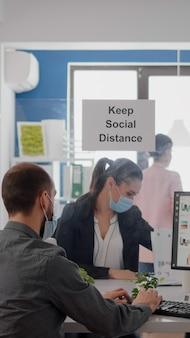 Empresarios que analizan gráficos financieros mientras trabajan después del bloqueo en una nueva oficina comercial con una mascarilla protectora para prevenir la infección por coronavirus