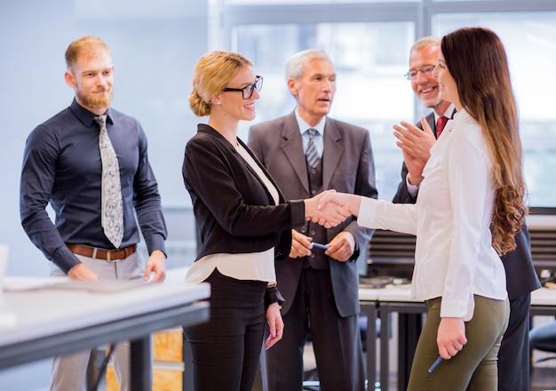 Empresarios que aplauden a la empresaria sonriente dos que sacude las manos