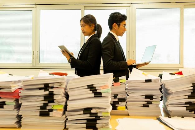 Empresarios que se colocan espalda con espalda con la pila de papeleo en primero plano.