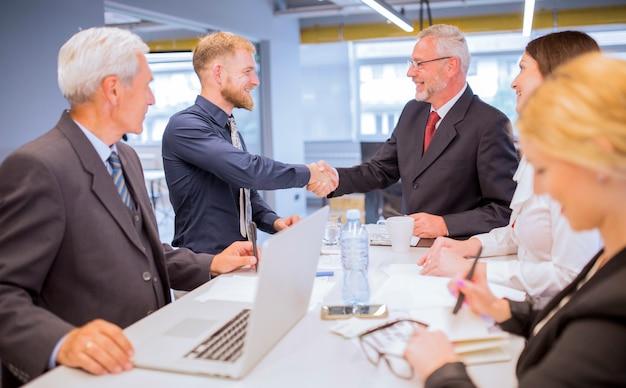 Empresarios que miran a dos hombres de negocios que sacuden las manos en la reunión de negocios