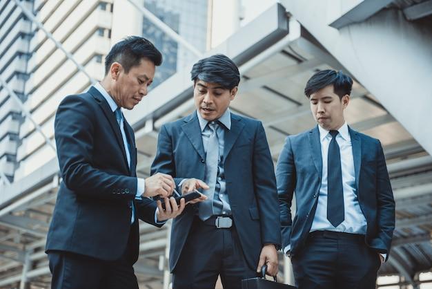 Empresarios que usan el teléfono móvil en el pasillo de un centro de negocios, pronunciado desenfoque de movimiento