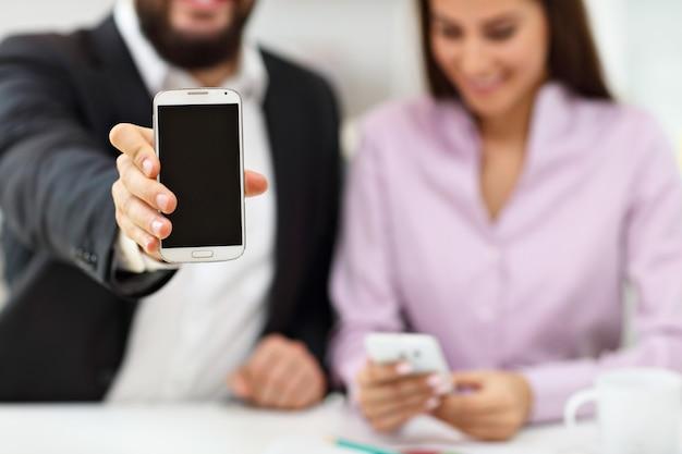 Los empresarios que utilizan sus teléfonos inteligentes en la oficina