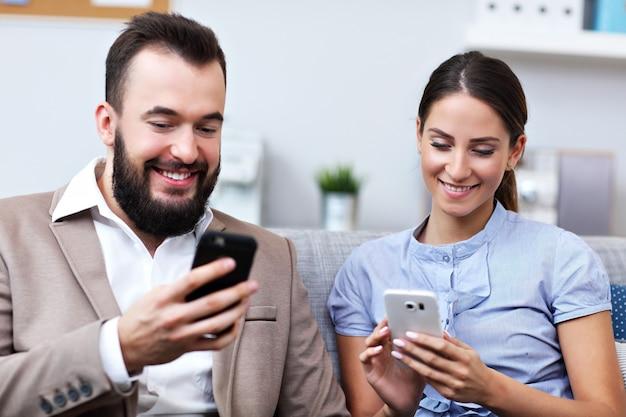 Empresarios que utilizan teléfonos inteligentes en la oficina