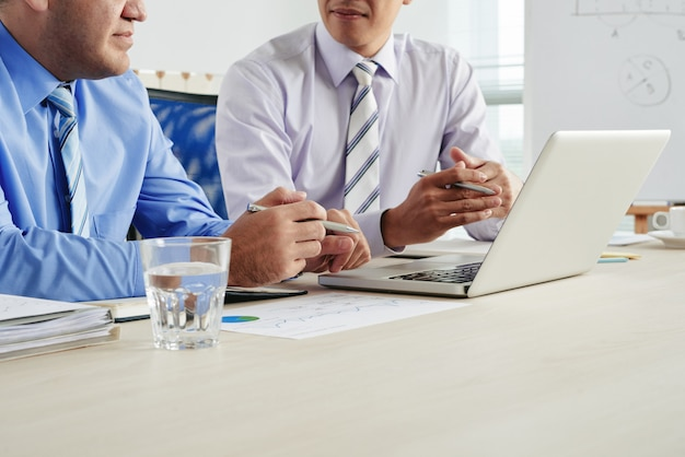 Empresarios recortados discutiendo cooperación en una reunión con vaso de agua, documentos y computadora portátil en el escritorio
