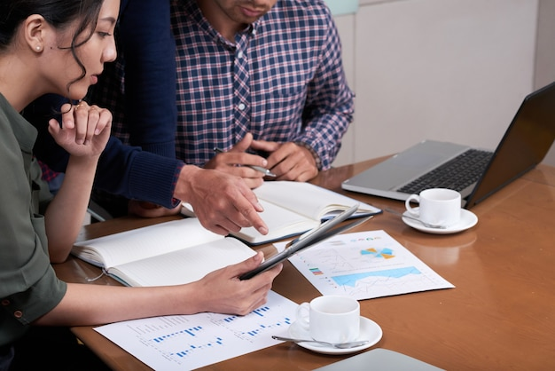 Empresarios recortados discutiendo gráficos y diagramas en la oficina