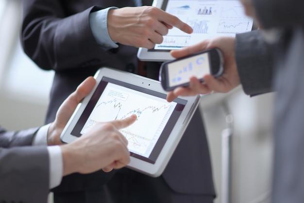 Empresarios en reunión presentando gráficos en smartphone, tableta