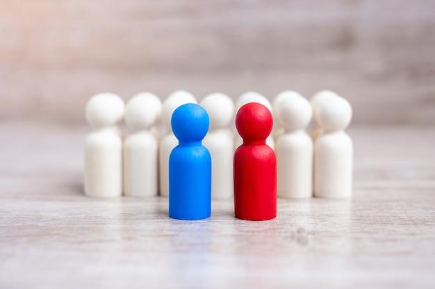 Empresarios rojos y azules con multitud de hombres de madera. candidato, liderazgo, negocios, equipo, trabajo en equipo y gestión de recursos humanos.