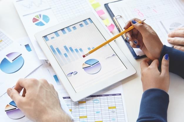 Empresarios sentados a la mesa con panel táctil y notas, desarrollando estrategias comerciales, realizando cambios en el informe financiero.