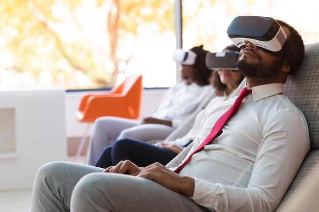 Empresarios serenos que disfrutan de la experiencia de realidad virtual