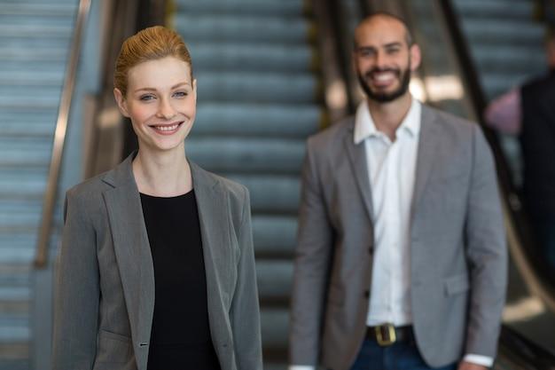 Empresarios sonrientes con equipaje de pie delante de una escalera mecánica