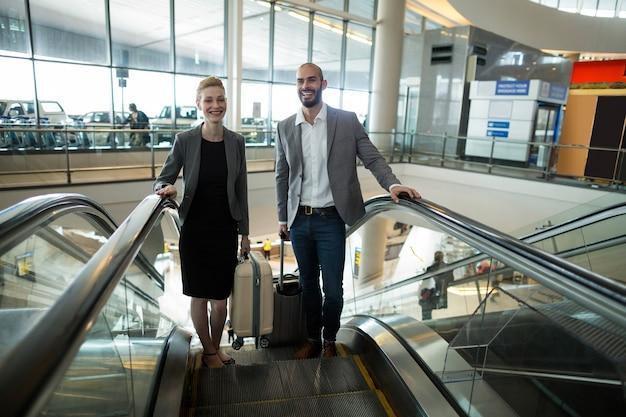 Empresarios sonrientes con equipaje subiendo escaleras mecánicas