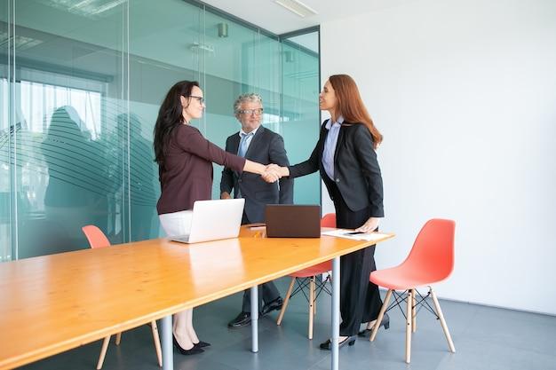 Empresarios sonrientes de pie y reunidos en la sala de conferencias