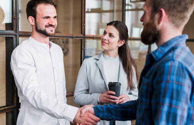 Empresarios sonrientes que sacuden la mano en la oficina