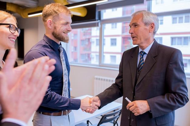 Empresarios sonrientes que sacuden las manos durante una reunión en la oficina