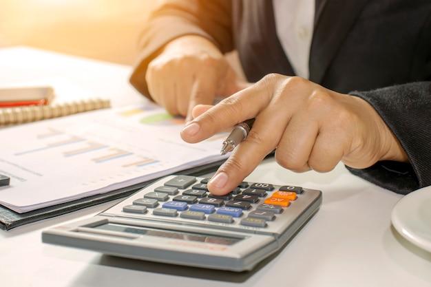 Los empresarios sostienen la pluma para presionar las ideas de contabilidad de la calculadora.