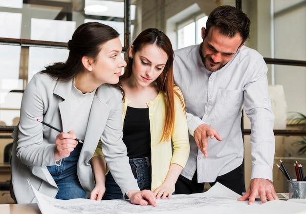 Empresarios trabajando en el plano azul en el lugar de trabajo