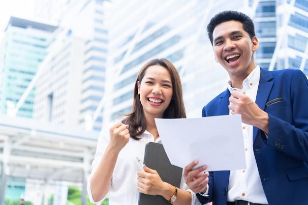 Empresarios trabajo en equipo levantando el brazo extendido junto con sentimiento de felicidad después de completar goa
