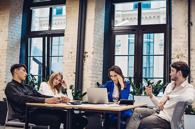 Empresarios tristes pensando en la mesa en la oficina