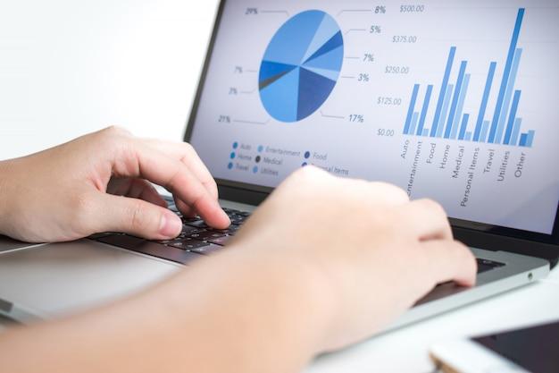 Los empresarios usan computadoras portátiles para analizar estadísticas.