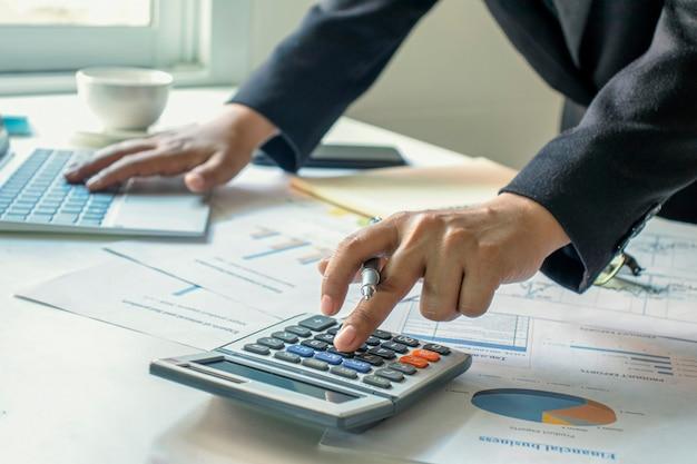 Los empresarios utilizan una calculadora para verificar su información financiera, ideas de trabajo y estrategias de trabajo en equipo.