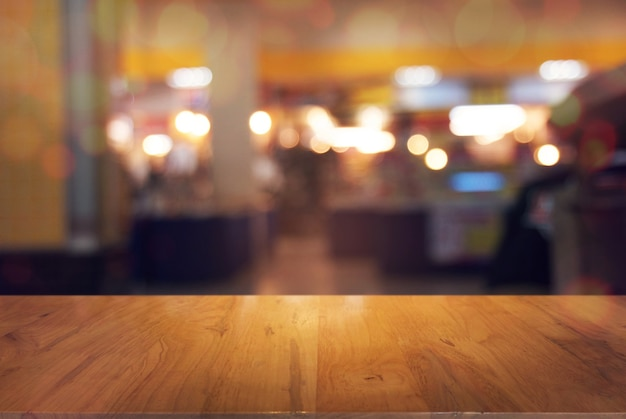 Empty mesa de madera delante de fondo abstracto borrosa de cafetería. puede ser utilizado para la exhibición o el montaje de sus productos. mueva para arriba para la exhibición del producto