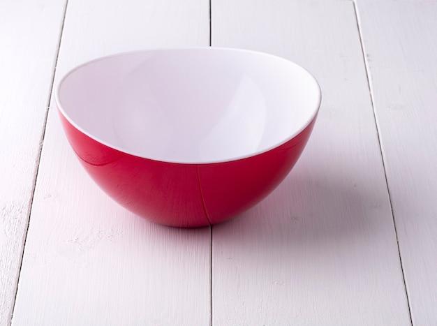 Empy red bowl sobre mesa de madera blanca