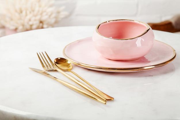 Emty comida rosa utensilios de cocina. utensilios de cocina con estilo en la mesa de mármol claro con espacio de copia. cartel en venta. utensilios de cocina modernos para postre o almuerzo. plato y tazón rosa