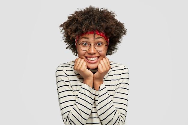 Encantada y complacida niña africana con gafas transparentes tiene una encantadora sonrisa amistosa, mantiene ambas manos debajo del mentón