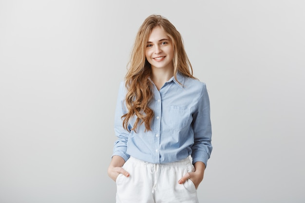 Encantado de conocer al nuevo equipo. retrato de mujer europea atractiva de aspecto agradable con cabello rubio en blusa azul formal, tomados de la mano en los bolsillos, escuchando al cliente mientras trabaja en la oficina