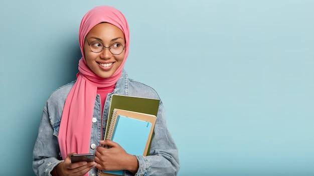 Encantado y feliz estudiante musulmán escribe mensajes en el teléfono celular, lleva un bloc de notas, se concentra a un lado con expresión alegre, usa una chaqueta de jean, aislada contra una pared azul, lee un artículo interesante