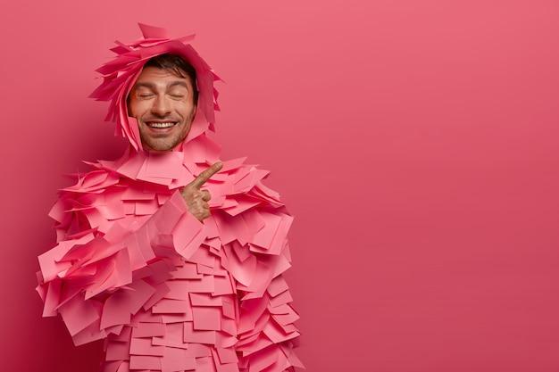 Encantado de hombre caucásico con expresión positiva divertida indica en el espacio en blanco, anuncia algo con buen humor, viste un traje de papel hecho de notas adhesivas, posa contra la pared rosada