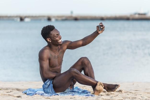 Encantado de hombre negro tomando selfie en la playa
