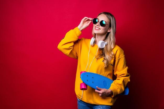 Encantado de mujer joven con patineta en el hombro y sonriendo contra la pared roja