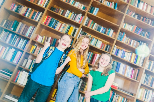 Encantado de niños sonrientes de pie en la biblioteca de la escuela