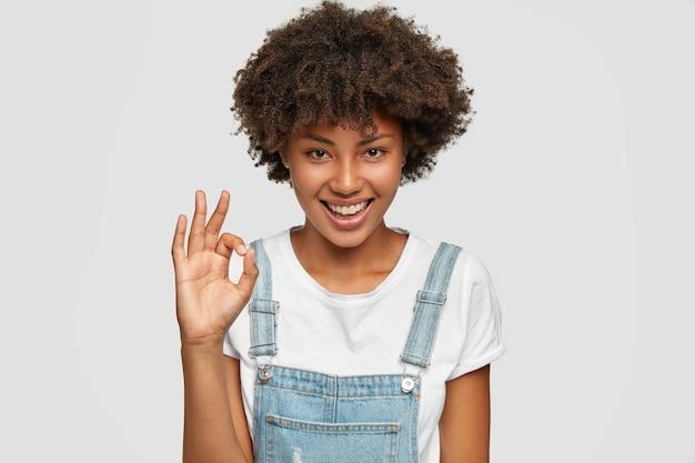 Encantado, satisfecho, seguro de sí mismo, adolescente afroamericano muestra un buen signo con una mano