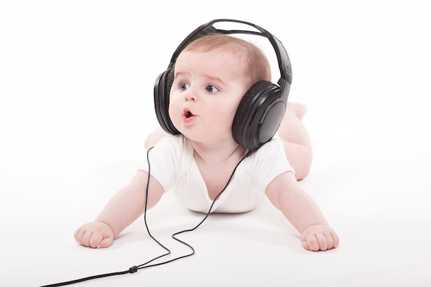 Encantador bebé en un blanco con auriculares escuchando música.