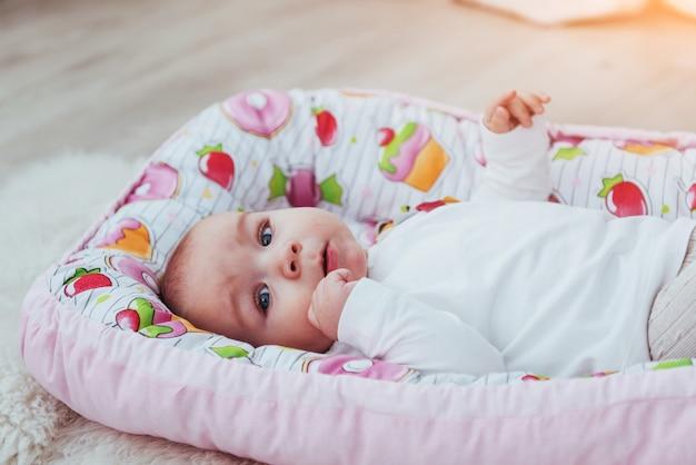 Encantador bebé recién nacido en una cuna rosa