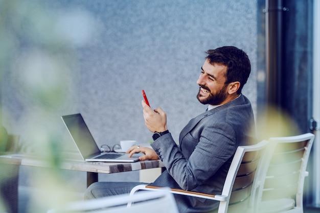 Encantador empresario barbudo caucásico sonriente en traje con teléfono inteligente mientras está sentado en la cafetería. en la mesa hay una computadora portátil y un café.