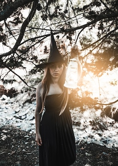 Encantador encantador que sostiene la linterna encendida en bosque soleado