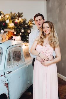 Encantador esposo abrazando a hermosa mujer rubia con vestido rosa.