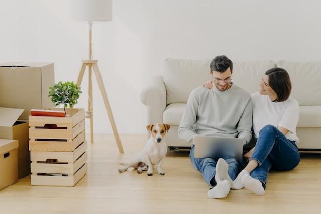 Encantador esposo y esposa se sientan en un nuevo apartamento con computadora portátil