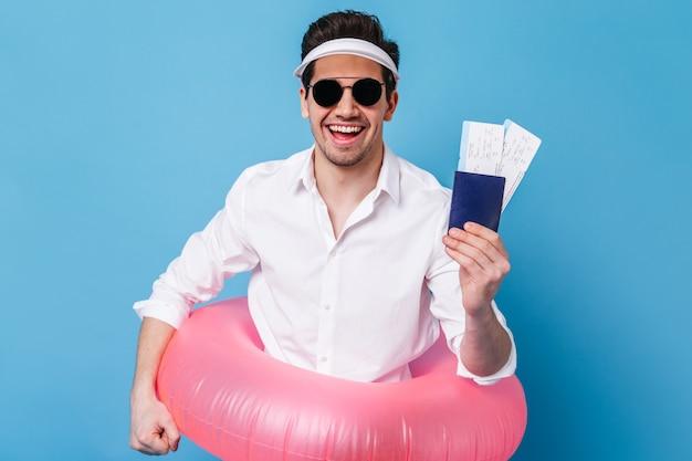 Encantador joven en camisa blanca clásica, gafas de sol y gorra sonríe con alegría y sostiene documentos, círculo inflable.