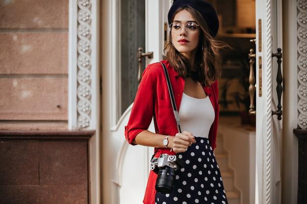 Encantador joven fotógrafo con cabello ondulado morena en boina, top blanco, camisa roja y falda de lunares de pie en la calle cerca de la cafetería y mirando a otro lado