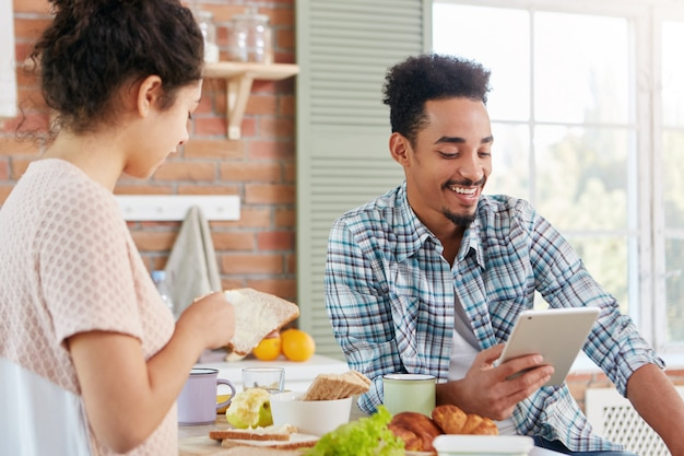 Encantador joven con piel oscura y cabello rizado lee historias divertidas en voz alta en una tableta mientras se sienta frente a la esposa que está ocupada