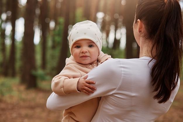 Encantador y lindo bebé infantil en manos de mamá mirando al frente