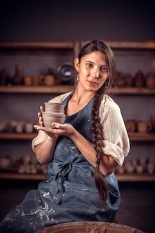 Encantador maestro femenino emplazamiento en un banco con torno de alfarería y haciendo olla de barro