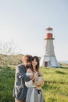 Encantadora abrazar feliz joven hipster elegante pareja enamorada caminando en el campo, moda boho de estilo veraniego