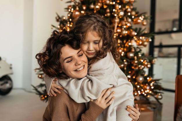 Encantadora adorable mujer caucásica con curvas abrazándose con su pequeña hija y celebrando la navidad y el año nuevo