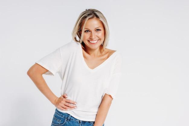 Encantadora amigable rubia sonriente mujer de 35 años en camiseta blanca y jeans azul mirando a la cámara aislada sobre fondo blanco, maqueta