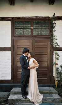 Encantadora y atractiva novia y el novio de pie cerca uno del otro en la casa antigua, foto de boda, pareja hermosa, día de la boda.